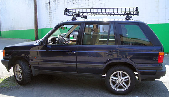 1999 Land Rover Range Rover cargo basket roof rack, Yakima Q88 Clips, Yakima Q Towers, Yakima 48 Inch Cross Bars, Yakima 4 Pack SKS Cores, Yakima MegaWarrior, Yakima MegaWarrior Extension, Yakima Locking Bracket