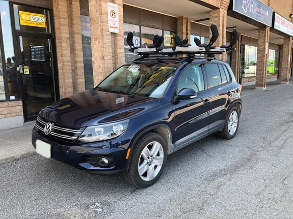 Volkswagen Tiguan 2016 with the Thule 450R Evo Wingbar Crossbars in black and two Thule Hullavator 898 Pro Kayak Carriers